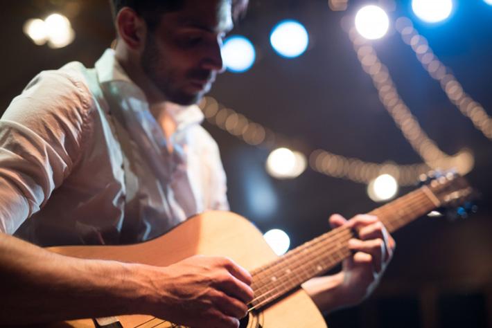 ステージで演奏するギタリスト