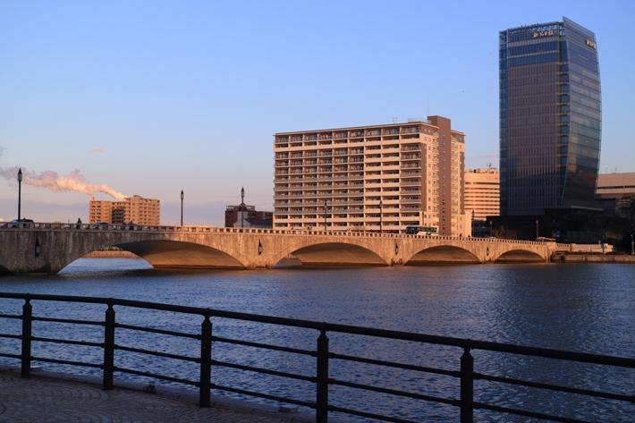 川岸から見た、夕日に染まる萬代橋
