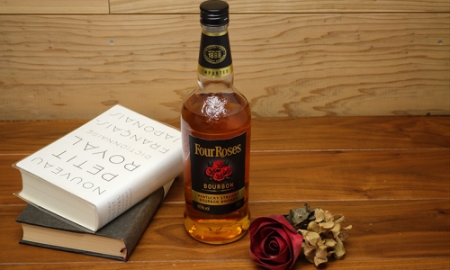 ウイスキーのボトルと本とバラの造花