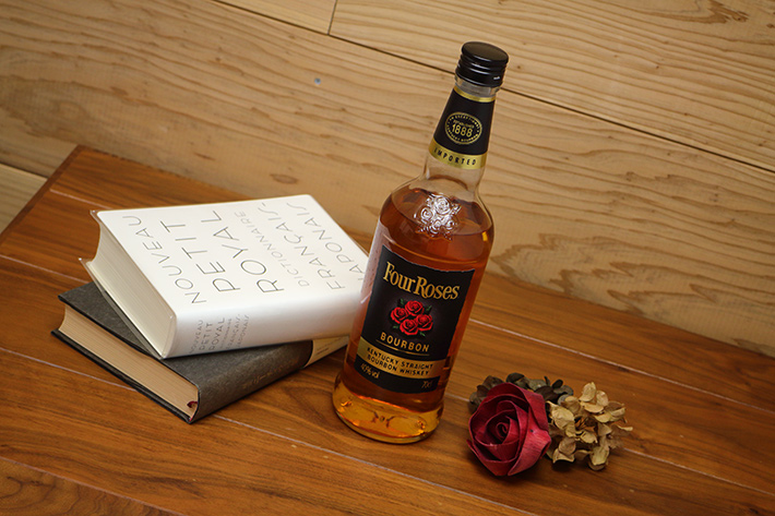 A liquor bottle and books taken with top lighting